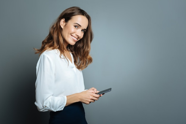 Technologie moderne. femme agréable ravie positive souriant et à l'aide de son smartphone lors de la messagerie en ligne