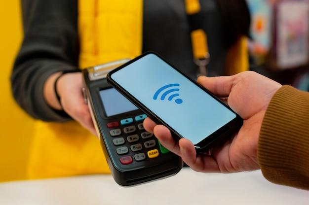 Technologie nfc un acheteur masculin tient un smartphone avec paiement sans fil dans ses mains.