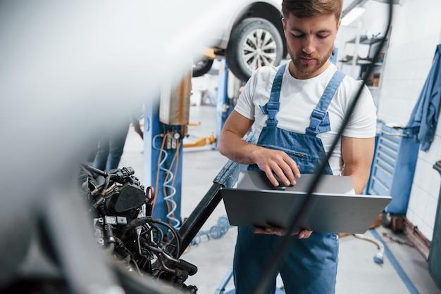 Technologie sans fil. l'employé en uniforme de couleur bleue travaille dans le salon automobile.