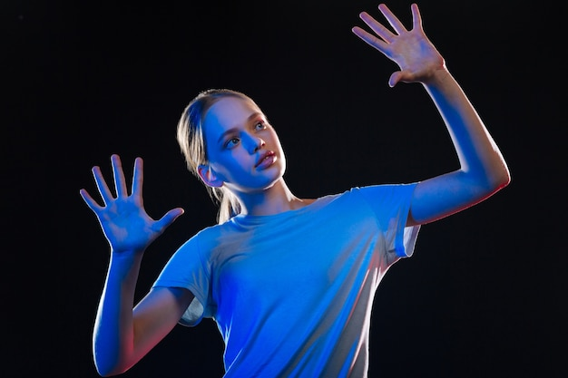 Technologie transparente. jolie femme blonde debout devant l'écran sensoriel tout en regardant ses mains