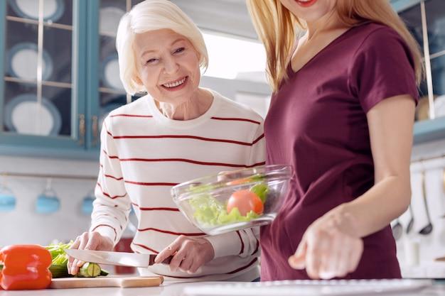 Technologie utile. charmante jeune femme et sa mère âgée faisant une salade de légumes et vérifiant la recette sur une tablette en souriant
