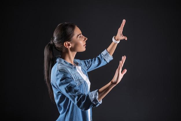 Technologie virtuelle. jolie femme agréable agréable debout et regardant ses mains tout en étant en réalité virtuelle