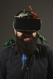 Technologie de vision 3d, lunettes de réalité virtuelle. concept d'aventure et de voyage virtuel - un homme barbu avec des lunettes de réalité virtuelle 3d aime voyager à l'ère des dinosaures. période jurassique. parc des dinos.