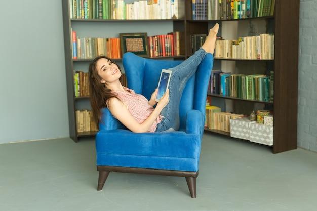 Technologies, concept de personnes - jeune fille assise sur une chaise et regardant la tablette ou surfer sur la