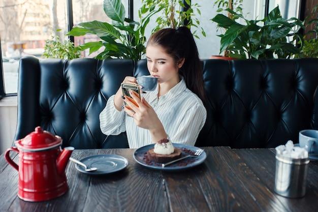 Technologies, émotions, mode de vie, personnes, concept d'adolescent - jeune femme heureuse lisant sur son téléphone portable alors qu'elle était assise dans l'intérieur d'un café moderne, fille avec un beau sourire. boire du thé