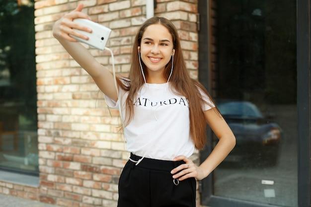 Technologies, émotions, personnes, beauté, mode et concept de style de vie - ambiance printanière ensoleillée et insouciante. une charmante jeune femme fait un selfie sur un appareil photo. lors d'une promenade en ville en plein air