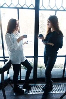 Technologies, mode de vie, nourriture, personnes, adolescents et concept de café - deux jeunes femmes prenant un selfie avec un téléphone intelligent dans le centre-ville. concept de bonheur sur les gens, boire du thé