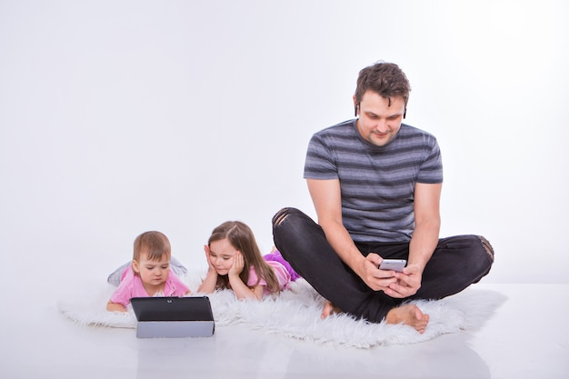 Les technologies modernes au quotidien: un homme parle au téléphone via un casque, des enfants regardent un dessin animé sur une tablette.