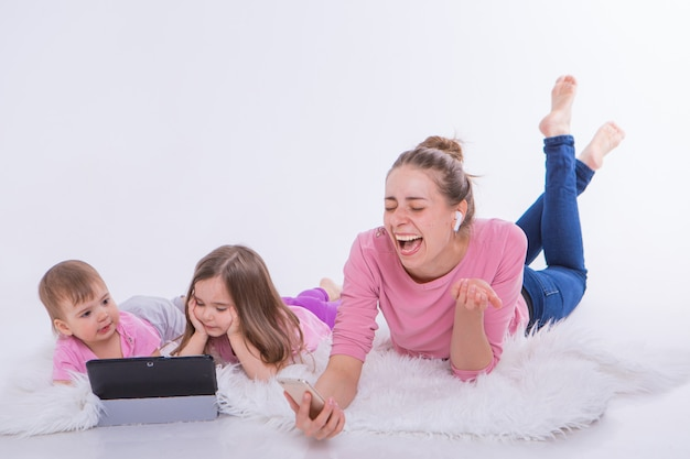 Les technologies modernes dans la vie quotidienne: une femme parle au téléphone via un casque, les enfants regardent un dessin animé sur une tablette. passe-temps et loisirs avec des gadgets. vacances en famille. parents avec des filles sur le sol
