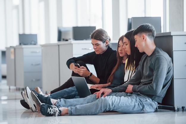 Les technologies modernes facilitent la vie. groupe de jeunes en vêtements décontractés travaillant dans le bureau moderne
