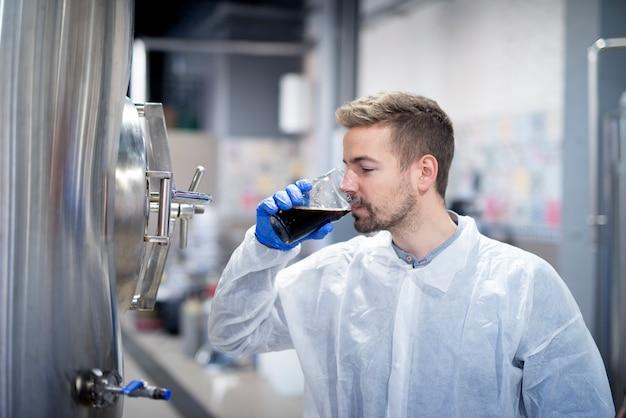 Technologue dégustant la qualité de la bière dans une brasserie moderne