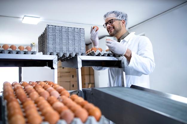 Technologue inspectant et vérifiant la qualité d'un œuf dans une usine de transformation des aliments.