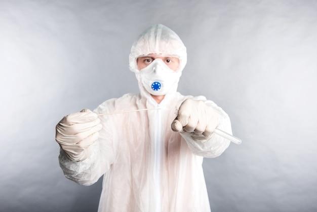 Technologue médical avec kit de prélèvement d'écouvillons covid-19, portant des gants de masque de protection blancs ppe, tube de prélèvement d'échantillons de patient op np, processus de protocole de test adn pcr