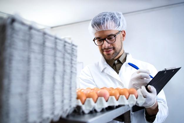 Technologue d'usine alimentaire contrôlant la production d'œufs à l'usine de transformation des aliments.