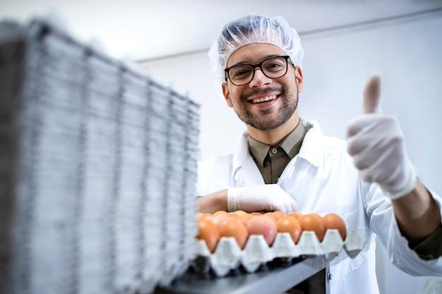 Technologue d'usine alimentaire debout près de la machine d'emballage d'oeufs industriels et tenant les pouces vers le haut.