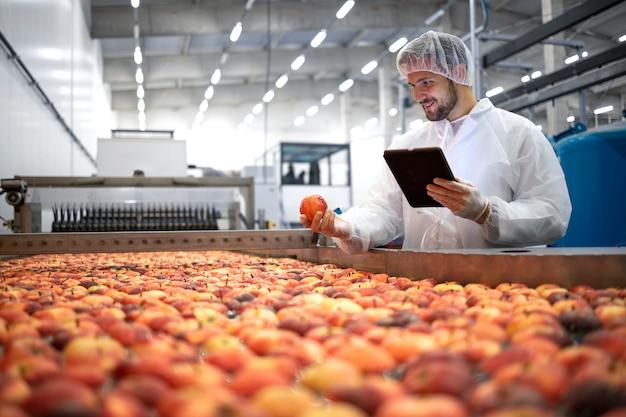 Technologue en usine de transformation des aliments contrôlant le processus de sélection et de production des pommes.