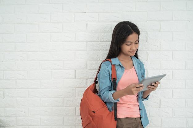 Teen asiatique tenant la tablette et debout