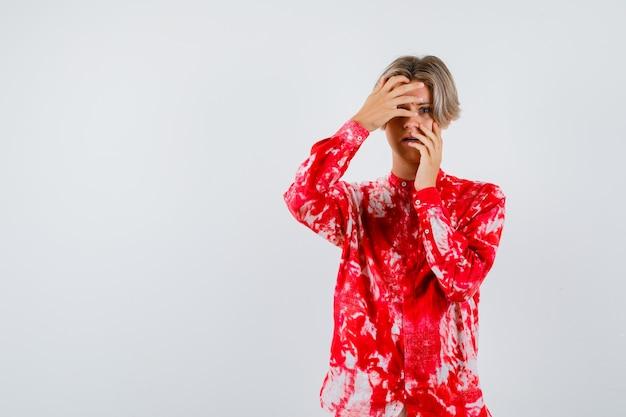 Teen blonde mâle en chemise surdimensionnée avec les mains sur le visage et l'air concentré, vue de face.