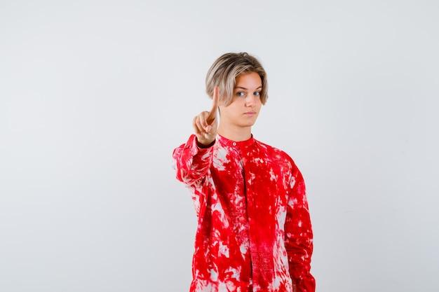 Teen blonde male en chemise surdimensionnée pointant vers la caméra et regardant pensive, vue de face.