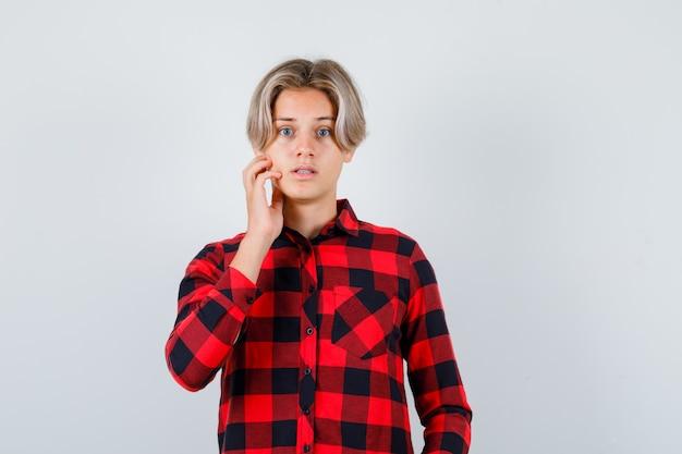 Teen blonde male gardant la main sur le visage en chemise décontractée et l'air surpris. vue de face.