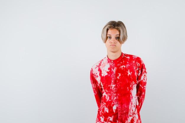 Teen blonde male avec les mains derrière le dos en chemise surdimensionnée et à la colère