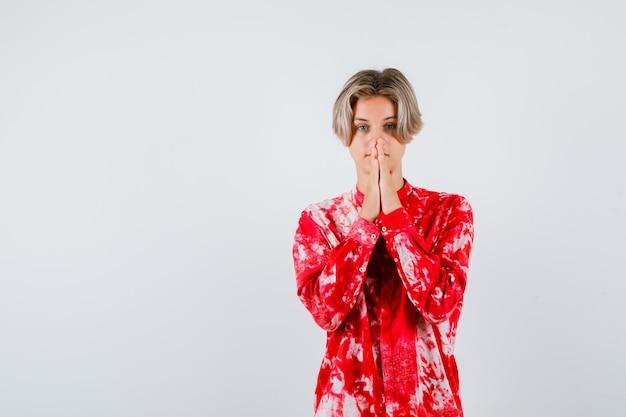 Teen blonde male avec les mains en geste de prière en chemise surdimensionnée et à l'espoir. vue de face.