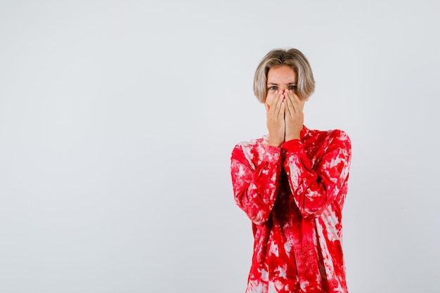 Teen blonde male avec les mains sur le visage en chemise surdimensionnée et à la curiosité. vue de face.