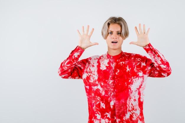 Teen blonde male montrant un geste d'abandon en chemise surdimensionnée et l'air abasourdi. vue de face.