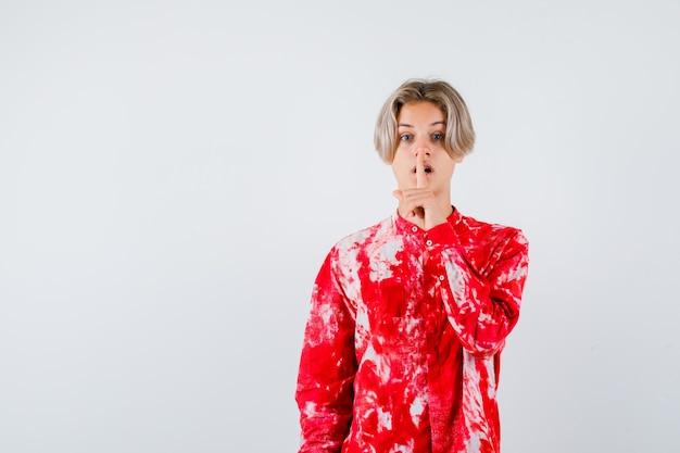 Teen blonde male montrant un geste de silence en chemise surdimensionnée et regardant concentré, vue de face.