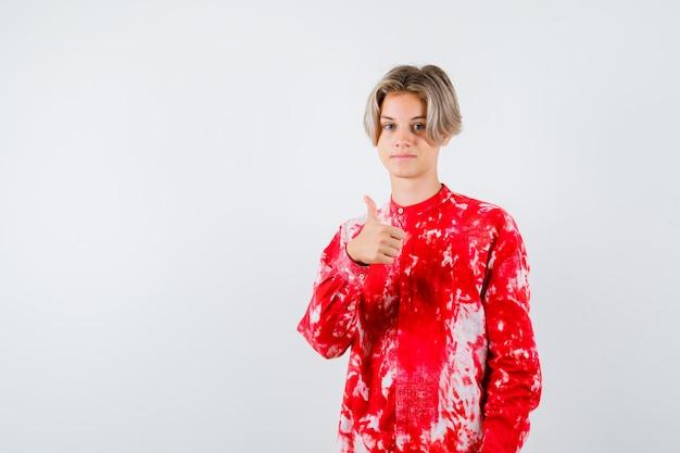 Teen blonde male showing thumb up en chemise surdimensionnée. vue de face.
