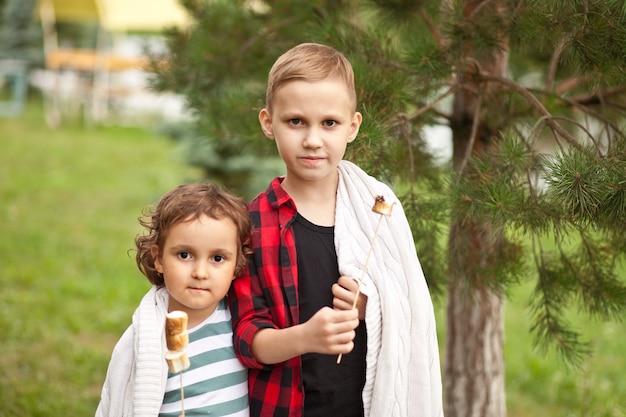 Teen boy and girl kid manger du marshmalloy rôti en plein air dans un camp. voyage, randonnée, vacances, concept de camping.