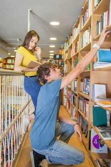Teen boy atteindre une étagère en cherchant un livre près de la petite amie