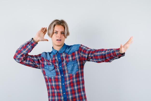Teen boy en chemise à carreaux gardant les mains pour se défendre et l'air anxieux, vue de face.