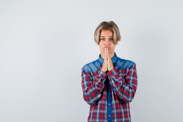 Teen boy en chemise à carreaux avec les mains en geste de prière et à l'espoir, vue de face.