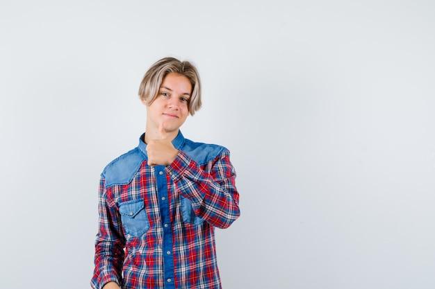 Teen boy en chemise à carreaux montrant le pouce vers le haut et l'air heureux , vue de face.