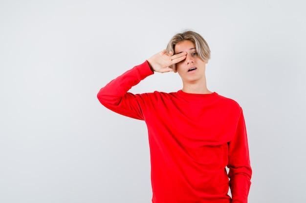 Teen boy holding doigts sur son œil, ouvrant la bouche en pull rouge et l'air surpris. vue de face.