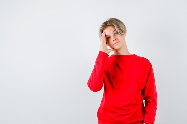 Teen boy in red sweater gardant la main sur la tête et l'air fatigué , vue de face.