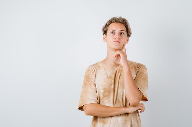 Teen boy in t-shirt debout en pensant pose et à la pensive , vue de face.