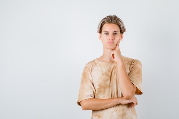 Teen boy in t-shirt gardant les doigts sur la joue et à la réflexion, vue de face.