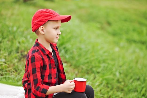 Teen boy kid en chemise à carreaux tenant une tasse de boisson. voyage, randonnée, vacances, concept de camping.