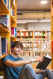 Teen boy avec livre en regardant la caméra