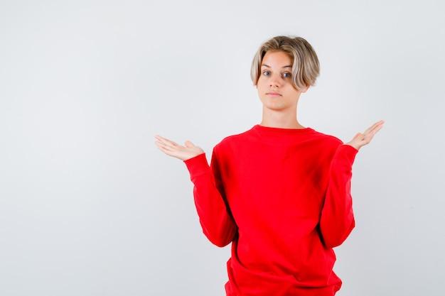 Teen boy montrant un geste impuissant en pull rouge et à la recherche d'indécis, vue de face.