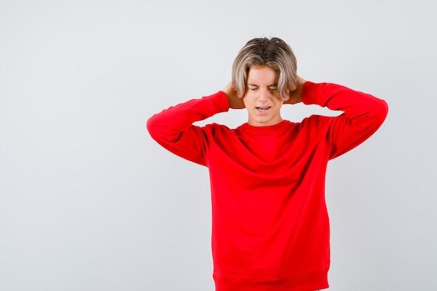 Teen boy en pull rouge avec les mains derrière la tête, fermant les yeux et l'air stressé, vue de face.