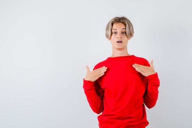 Teen boy en pull rouge avec les mains sur la poitrine et l'air étonné , vue de face.