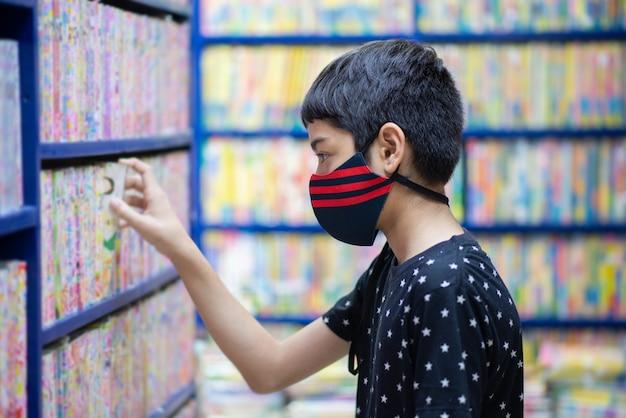 Teen boy à la recherche de livres à acheter à la librairie
