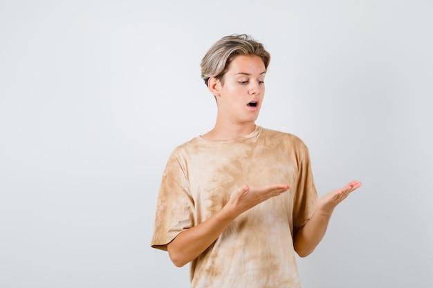 Teen boy regardant ses paumes, ouvrant la bouche en t-shirt et l'air étonné, vue de face.