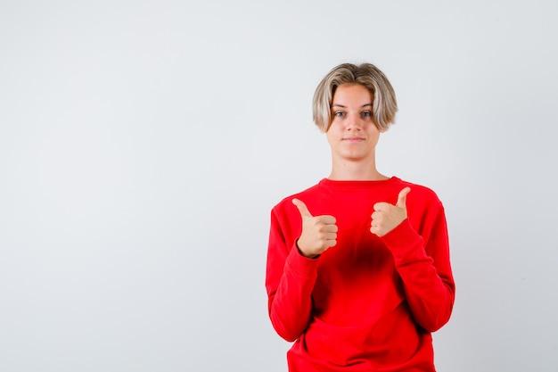 Teen boy showing thumbs up en pull rouge et l'air heureux. vue de face.