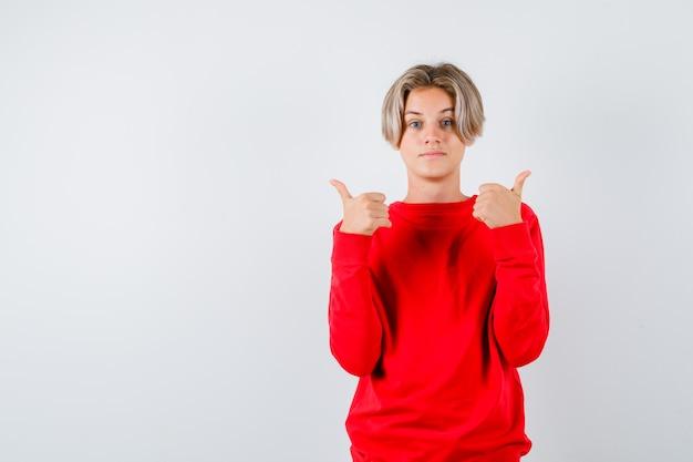 Teen boy showing thumbs up en pull rouge et l'air satisfait. vue de face.