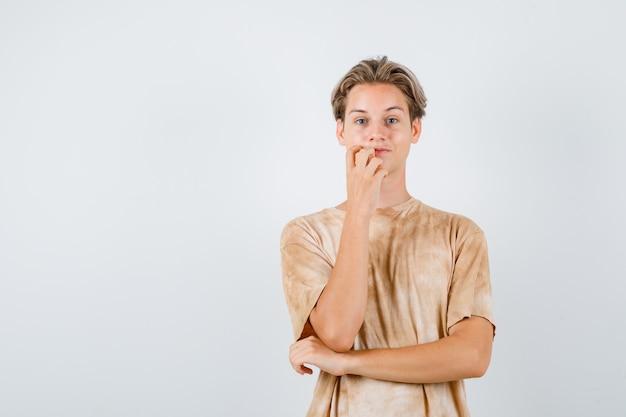 Teen boy standing in pensant pose en t-shirt et à la réflexion , vue de face.