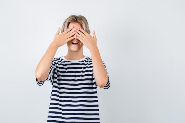 Teen boy en t-shirt couvrant les yeux avec les mains, ouvrant la bouche et l'air excité, vue de face.